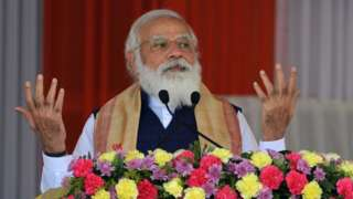 Prime Minister Narendra Modi gestures as he addresses a public meeting at Jerenga Pathar in Sivasagar district of India's Assam state on January 23, 2021.