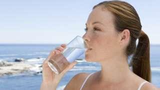 Mujer bebe agua en un vaso con el mar de fondo.