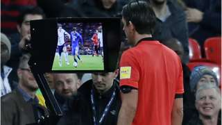 A referee refers to VAR during the World Cup in Russia