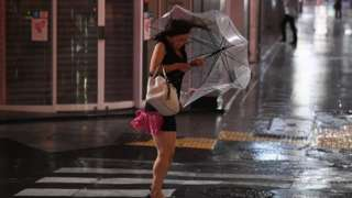 A woman struggles with an umbrella in the wind and rain
