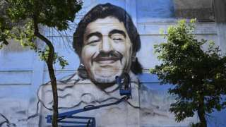 An artist uses a crane to paint a large mural of Maradona on the side of a building