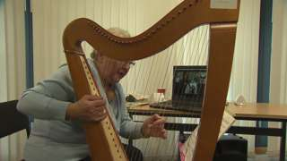 Elinor Bennett with harp and laptop