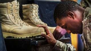 soldado americano cabisbaixo segura em duas botas de combate que estão à sua frente