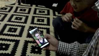 Mujtaba Qalandari holds a phone with a picture of Ali Joya
