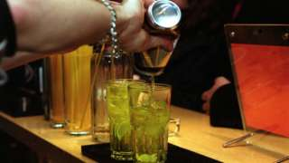 A barman pouring drinks in Fluid bar, 40 Charterhouse Street in Clerkenwell, London.