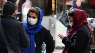 Women wearing face masks stand in a street in Tehran, Iran (26 February 2020)