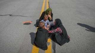 Afghan people sit along the tarmac as they wait to leave the Kabul airport