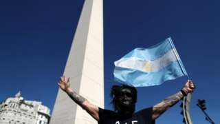 "A demonstrator wearing a gorilla face mask waves an Argentine flag as he takes part in a protest against Argentina""s national government amid the coronavirus disease (COVID-19) outbreak, at the obelisk in Buenos Aires, Argentina, October 12, 2020"