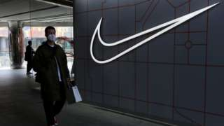 A man walks past a store of the sporting goods retailer Nike Inc at a shopping complex in Beijing.