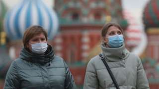 Women in protective masks walk in Red Square during the Covid-19 pandemic