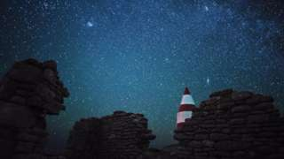 Stars over rocky walls and a lighthouse