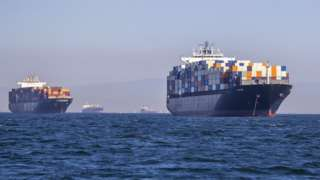 Two full container ships, and two more in the background, in the water outside Los Angeles ports