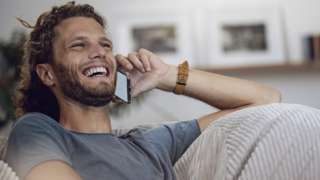 A man laughs while talking on the phone in this stock image