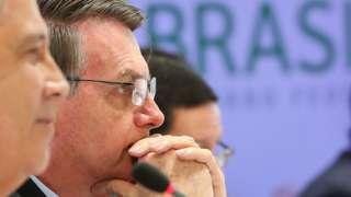 Bolsonaro de perfil, ao lado de dois ministros, em reunião