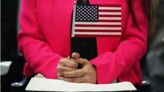 Woman holds flag during naturalisation ceremony