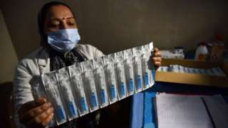 Health care worker in Jammu holds syringes with a mock Covid vaccine (2 Jan)