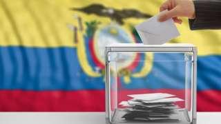 mão coloca cédula em urna de votação