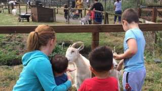 Family petting a goat
