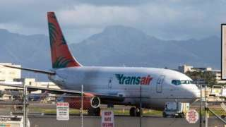A Transair 737 cargo plane on the runway in Hawaii
