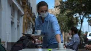 Woman serving coffee outside a bar