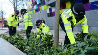 Police officers look for evidence in London