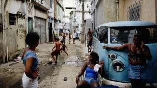 Mulheres conversam apoiadas em uma caminhonete enquanto crianças brincam ao fundo na favela do Jacarezinho, nos anos 1990