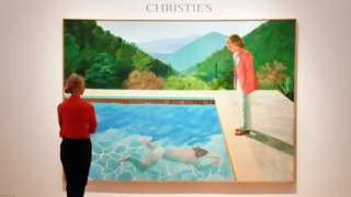 """A woman looks at David Hockneys """"Portrait of an Artist (Pool with Two Figures)"""" during a press preview on September 13, 2018 at Christie""""s New York."""
