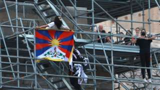 A protester holds a Tibetan flag during a demonstration at the Acropolis Propylaea, in Athens, Greece, October 17, 2021.