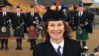 Irene Robinson standing in front of a group of pipers