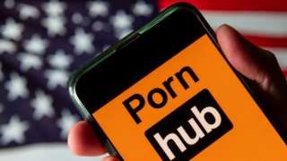 The Pornhub logo is seen on a mobile phone screen held by a hand in front of an American flag