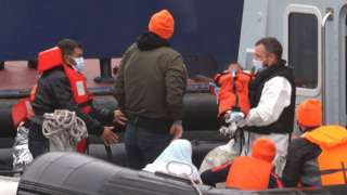A small child is lifted off a Border Force vessel at the port of Dover