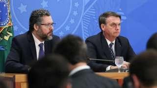 Ernesto Araújo e Bolsonaro lado a lado em mesa de evento em ambiente interno