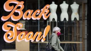 Woman in mask walks past closed shop with the words 'Back Soon!' on the window