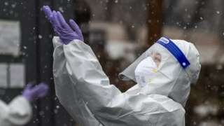 A health worker wearing a protective suit enjoys falling snow at a coronavirus disease (COVID-19) testing site in Seoul, South Korea, January 12, 2021.