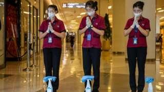 Nhân viên của Siam Paragon Mall, Bangkok Thailan, mang thiết bị bảo vệ đứng vái chào khách hôm 17/5