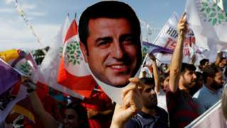 "A supporter of Turkey""s main pro-Kurdish Peoples"" Democratic Party (HDP) holds a mask of their jailed former leader in 2018"