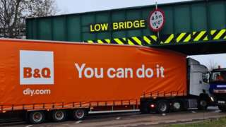 B&Q lorry bearing a logo that says 'you can do it' stuck under a bridge