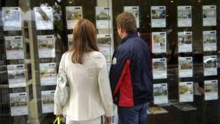 A couple, a woman in a white jacket and a man wearing a windbreaker, standing outside an estate agent looking in the window