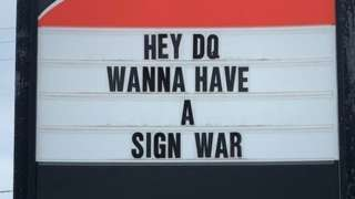 A sign reads 'Hey DQ, Wanna have a sign war'