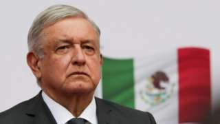 President Andres Manuel Lopez Obrador listens to the national anthem as he arrives to address the nation on his second anniversary as President of Mexico, at the National Palace in Mexico City, Mexico, December 1, 2020.