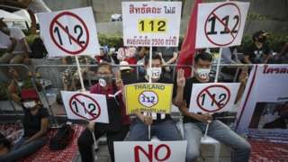 Anti-government protesters hold up placards during a rally calling to lift the section 112 of the Thai Criminal Code