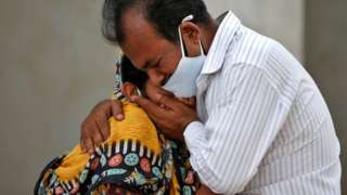 A woman is consoled by a relative outside a hospital in Ahmedabad, India, after her husband died from the coronavirus disease