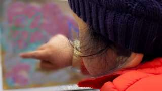 Child with learning disabilities points at picture