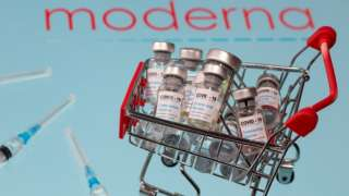 "A small shopping basket filled with vials labelled ""COVID-19 - Coronavirus Vaccine"" and medical syringes are placed on a Moderna logo in this illustration taken November 29, 2020"