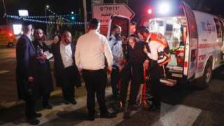 Israeli emergency forces evacuate injured ultra-Orthodox Jews after the collapse of seatinge in a synagogue, in the West Bank settlement of Givat Zeev (16 May 2021)