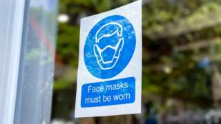 A sign asking people to wear masks