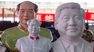 Porcelain statues of Mao Zedong and Xi Jinping on a market stall.