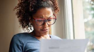 Woman looks concerned reading sheet of paper.