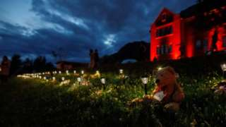 A teddy bear sits beside a lantern and momentous outside the former Kamloops Indian Residential School where flowers and cards have been left as part of a growing makeshift memorial to honour the 215 children whose remains have been discovered buried near the facility in Kamloops on June 5, 2021.