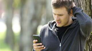 Man looking at his phone with a frustrated expression